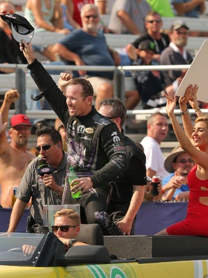Funny Car driver Jack Beckman of California celebrates with his fans after winning the Traxxas Funny Car Shootout against Robert Hight during the 61st Annual Chevrolet Performance U.S. Nationals held at Lucas Oil Raceway on Sunday, September 6, 2015. Beckman snagged the win as well as a $100,000 prize.