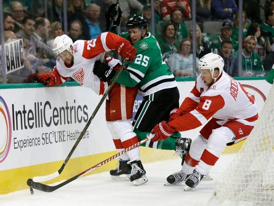 Detroit Red Wings defenseman Mike Green (25), Justin Abdelkader (8) and Dallas Stars right wing Brett Ritchie (25) compete for control of the puck in the first period of an NHL hockey game, Tuesday, Oct. 10, 2017, in Dallas. (AP Photo/Tony Gutierrez)