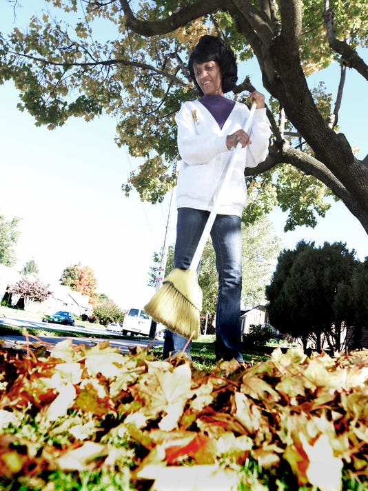 For lack of a rake, Ruby Newson clears her lawn with a broom outside her apartment Thursday, October 15, 2015. She said it worked just as well as a rake. Bill Kalina - bkalina@yorkdispatch.com