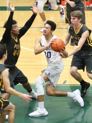 North Kitsap's Kai Warren (center) draws a foul on his way to basket in the fourth quarter Friday night against Fife in the Class 2A West Central District Tournament at Foss High in Tacoma.  The Vikings won 46-41 to qualify for regionals.