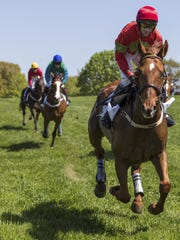 Jockeys race in The Winterthur Bowl as onlookers line the nearly 3-mile course to watch during the 2013 Point-to-Point races.