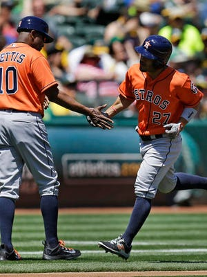Houston Astros' Jose Altuve, right, celebrates with third base coach Gary Pettis (10) after hitting a home run off Oakland Athletics' Rich Hill in the first inning of a baseball game, Sunday.