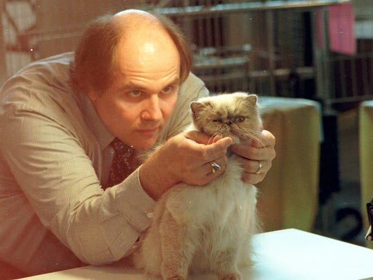 Donald Finger of Mosinee looks over a cat during the Central Wisconsin Cat Show in 199.