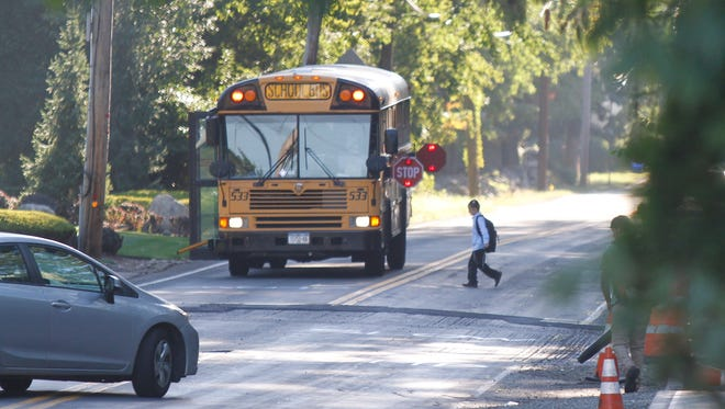 A boy crosses Grandview Avenue in Monsey to board a school bus Wednesday.