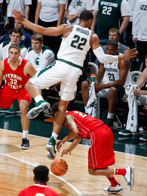 Michigan State's Miles Bridges (22) jumps over Ferris State's Jaylin McFadden during the first half of an NCAA college basketball exhibition game, Thursday, Oct. 26, 2017, in East Lansing, Mich. Bridges was injured on the play.