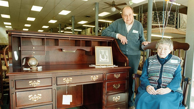Herman and Mary Frances Alles pose by a rolltop desk and a portrait of their late father Jacob Alles at their furniture store, Alles Brothers Furniture, Tuesday afternoon, March 16, 1999. Herman said his father was 90 years old in that picture, which was taken for an article The Gleaner did in 1949 about people who were still working after age 80. The late Alles pioneered the design for the rolltop desk that is common in many households.