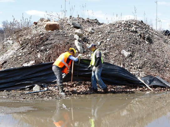 In this file photo, workers place containment fencing