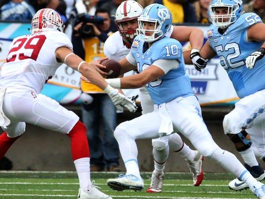 North Carolina quarterback Mitch Trubisky, 10, scrambles