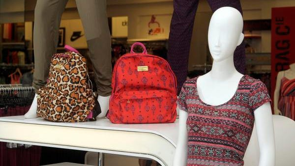 Printed Betsey Johnson backpacks alongside a mannequin donning a crop top and soft pants at Macy's in Visalia.
