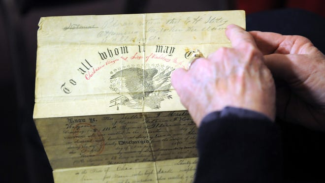 Mary Flanagan, patron of the Zanesville Museum of Art, holds out an ancestor's discharge papers from the Civil War during a class at the museum on how to preserve documents and heirlooms.