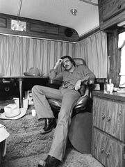 """FILE - In this Sept. 23,1976 file photo Burt Reynolds sits in his trailer on the set of """"Smokey and the Bandit,"""" in Atlanta.   Hundreds of fans in Trans Ams made it to Atlanta to celebrate the 40th anniversary of """"Smokey and the Bandit."""" About 350 cars retraced actor Burt Reynolds' wild ride from the Texas-Arkansas line to Atlanta in the movie that roared into pop culture in 1977. (Atlanta Journal-Constitution via AP)"""
