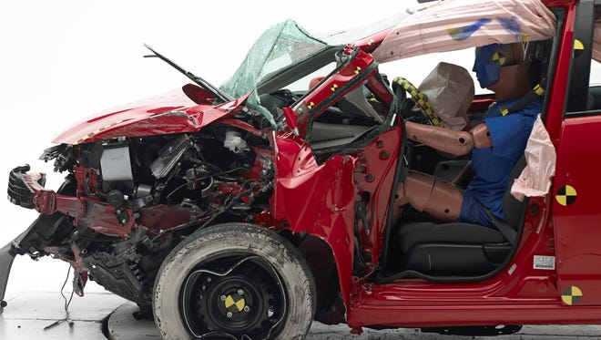 A Honda Fit after IIHS small overlap frontal crash test showing how the metal was pushed back toward the driver