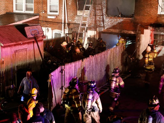Firefighters work at a Canby Park rowhouse at  3 a.m.