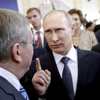 Russian President Vladimir Putin makes a point with International Olympic Committee President Thomas Bach, at a welcoming event for IOC members ahead 2014 Winter Olympics in Sochi, Russia.