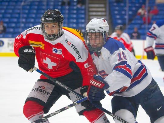 U.S. NTDP Under-18 forward Scott Reedy (No. 10) battles against Switzerland's Lionel Heughebaert (No. 8) during Tuesday's tournament game at USA Hockey Arena in Plymouth.