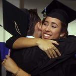 Marielizabeth Turmero gives Jose Tello a hug before the start of the Florida Gulf Coast University's summer graduation ceremony Sunday at Alico Arena.  Around 400 students were graduating at the ceremony which also involved the conferring of Masters and PHD's.  There were also a number of different programs represented such as Business and Arts and Sciences.