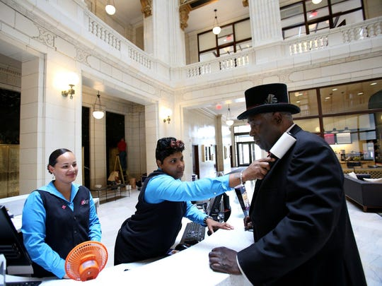Montina Adkins, 43, of Detroit helps get the lint off doorman Christopher Roddy's coat, as Eva Caraballo, 31, of Detroit looks on at the welcome desk in the David Whitney Building.