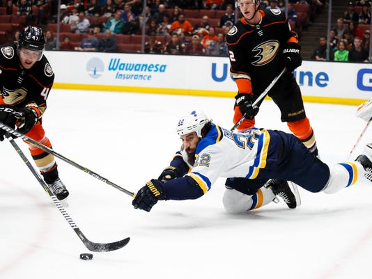St. Louis Blues' Chris Thorburn, center, falls to the ice as he reaches for the puck against Anaheim Ducks' Hampus Lindholm, left, of Sweden, during the first period of an NHL hockey game Monday, March 12, 2018, in Anaheim, Calif. (AP Photo/Jae C. Hong)
