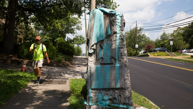 A person walks past a confederate monument which was recently defaced with paint in Fort Sanders near 17th Street and Laurel Avenue Knoxville Wednesday, Aug. 16, 2017.