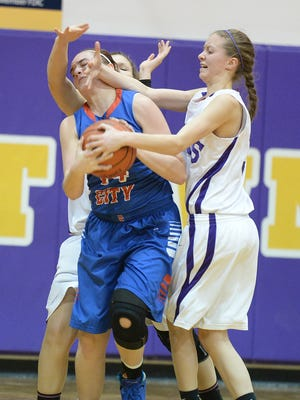 Hagerstown's Tawni Brown and Kaley Caudill, right, try to steal the ball from Union City's Raelynn Mills during a girls basketball game in Hagerstown Thursday, Feb. 6, 2014.
