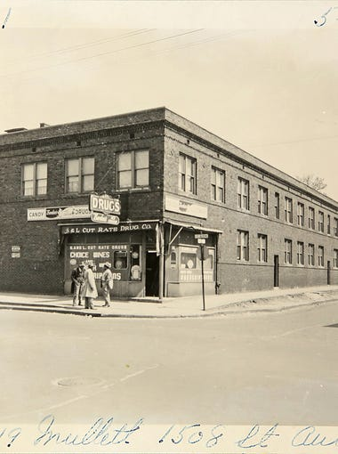 In this historical photo, a group stands outside of a drugstore on the corner of St. Aubin and Mullett streets on May 8, 1950 in Black Bottom, an area that was torn down in the 1950s to make way for the Chrysler Freeway and the Detroit Medical Center. Black Bottom is the ancestral neighborhood of many metro Detroit African-Americans.