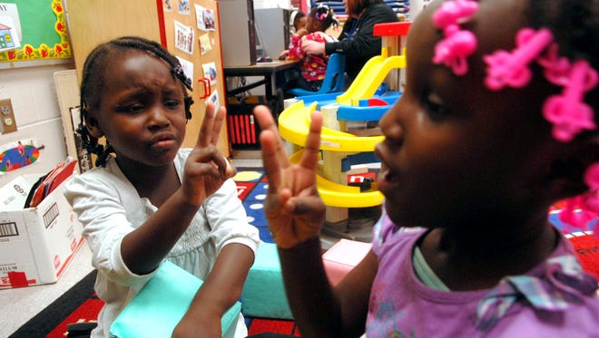 Sisters Faith Miles, 4, left, and Cherish, right, discuss how old they currently are at the Dawson Orman Eduction Center's Head Start class.  Jan. 26, 2015