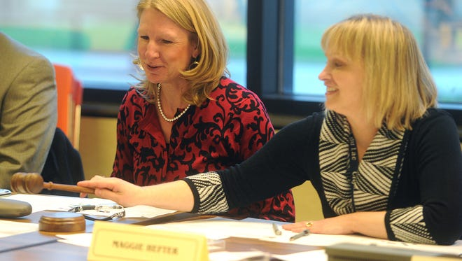 City Clerk Maggie Hefter slides the gavel over to newly elected president Lee Ann Lorrigan at a city council meeting Tuesday night. Tuesday April 21, 2015.