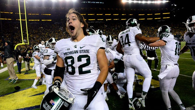 Michigan State tight end Josiah Price screams with unbridled joy as he celebrates with teammates after a thrilling, last-second 27-23 victory over Michigan Saturday in Ann Arbor.