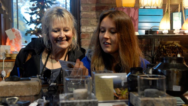 Carol Contratto, left, and her daughter, Angela, 22, right, look at gifts at Peace Of The Earth during Small Business Saturday on W. Market St. in NuLu.  Nov. 28, 2015