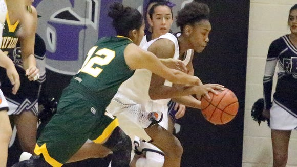 Nailah Blount, center, works to keep control of the