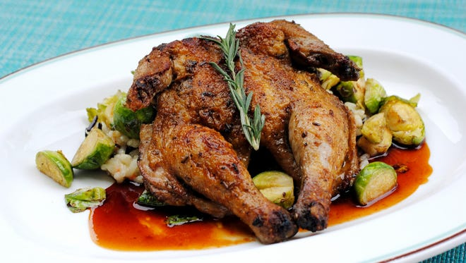 The herb roasted Cornish hen entree served with wild rice, grilled corn risotto and crispy brussels sprouts from Zuzu at Hotel Valley Ho.