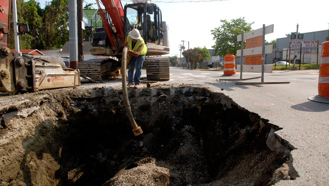 AJ Caldwell puts a hose in to drain the pipe at the intersection of Frankfort Ave. and Mellwood Ave. The street is expected to be closed for close to a month while crews from MSD clean and replace part of a nearly 147 year-old cast iron water main pipe.  June 12, 2016