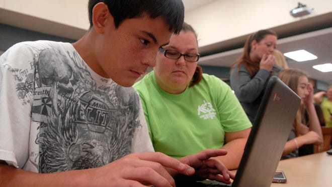 Incoming Bullitt Central High School freshman, Brandon Luna, 14, logs on to his new laptop as his mother, Elizabeth Olvera Perez, watches in this August 2016 photo.