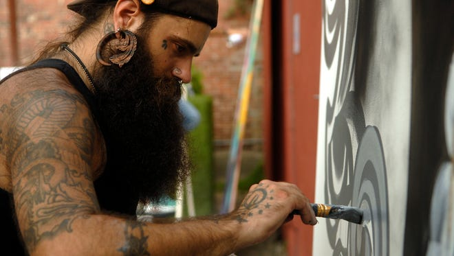 Vinnie Kochert works on a black and grey mural at the Mapped Out kick off event at Garage Bar in NuLu Friday evening. The party launched Louisville Visual ArtÕs Mural Art Program, MAP!. Local artists created 8ft x 8ft paintings available for purchase via silent auction. Aug. 19, 2016