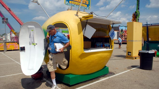 A health inspector pops out of a lemonade hut at the Kentucky State Fair's mid-way on Friday afternoon. Aug. 26, 2016