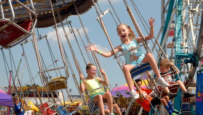 Ava Scheldorf, 7, rides the swings at the Kentucky State Fair's mid-way on Friday afternoon. Aug. 26, 2016