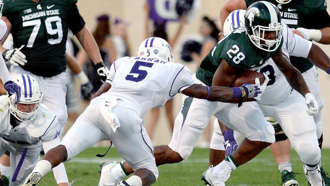 Michigan State University sophomore running back Madre London (28) explodes through a hole in the Paladin defense in the first half of play against Furman in the Spartan's opening game of the 2016 season Friday, Sept. 2, 2016, in East Lansing.