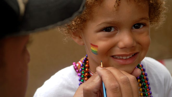 Xavier Ahlbrand, 3, right, has a rainbow flag painted on his face by volunteer Brain Mundy, left, at the second annual Louisville Pride Festival on Bardstown Road on Saturday afternoon. Sept. 17, 2016