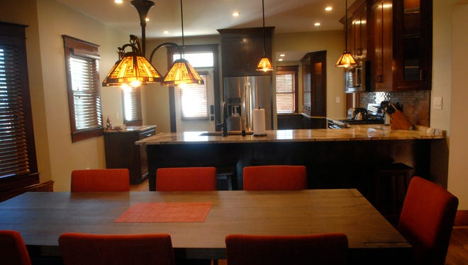 Arts & craft style chandelier over the long modern wood table surrounded by bright orange accent chairs in the dining area of the newly renovated Germantown home of Alex and Maria Raitz. Sept. 20, 2016