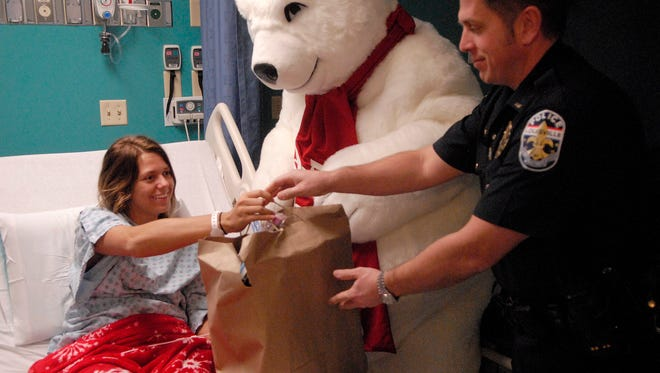 McKinley Scudder, 15, from Vevay, Ind. smiles as Lt. Les Skaggs hands her presents from the River City FOP and the Jeffersontown FOP at Norton Children's Hospital .  Dec. 19, 2016