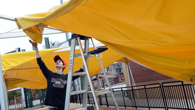 Facility assistant Peter Witherow hangs awnings in the right field Home Run Patio at PeoplesBank Park in preparation for the York Revolution's 2017 season. The Revs will hold a patio party at the facility this coming weekend. The John A. Pavoncello photo