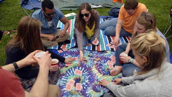 """Katie Moravec, center, passes out cards for a game of """"Irish Poker"""" while waiting for Thunder Over Louisville to start in  2016"""