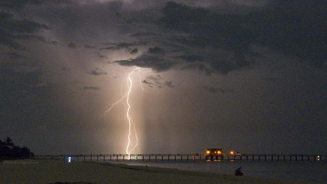 A lightning strike flares up along the Naples coast in 2009, illuminating the Naples Pier.
