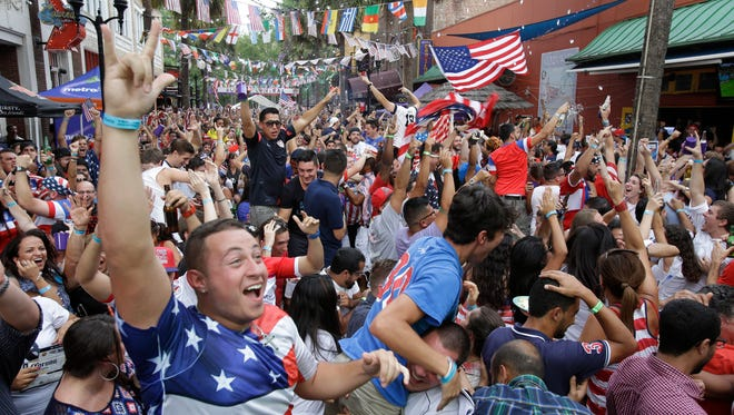 Fans cheer after the United States scored a goal against Portugal as they watch the World Cup soccer match on a big screen television in Orlando, Fla.