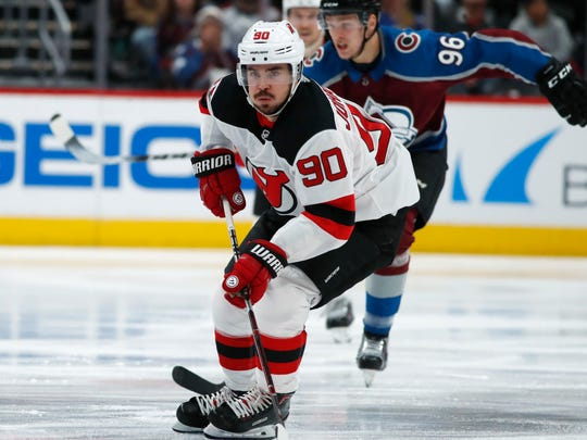 New Jersey Devils left wing Marcus Johansson, front, of Sweden, drives down the ice with the puck as Colorado Avalanche right wing Mikko Rantanen, of Finland, pursues in the second period of an NHL hockey game Friday, Dec. 1, 2017, in Denver. (AP Photo/David Zalubowski)