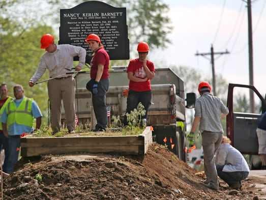 UIndy graduate students gently sift through dirt at
