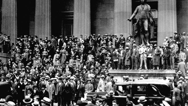People gather across the street from the New York Stock Exchange in New York Oct. 24, 1929. Thousands of investors lost their savings in the worst stock market crash in Wall Street history. The Great Depression followed.