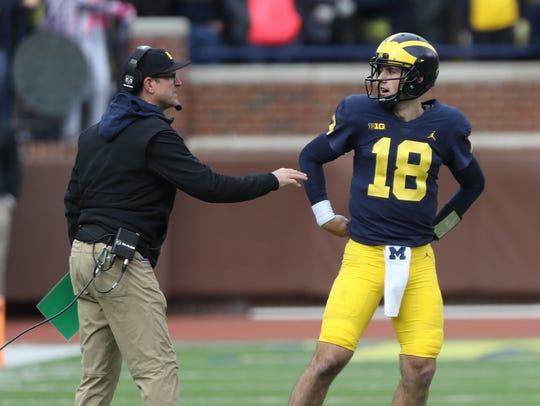 Jim Harbaugh talks with quarterback Brandon Peters