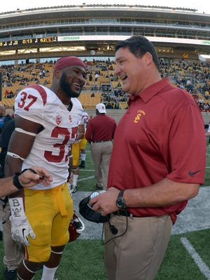 Southern California coach Ed Orgeron (right) and tailback Javorius Allen (37) celebrate after the Trojans routed California.