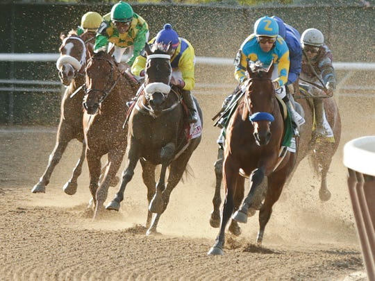 American Pharoah, with Victor Espinoza up, rounds the
